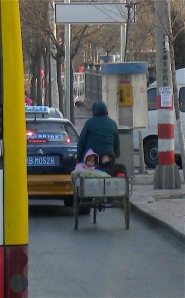 Slowing down: a mother and children caught in Beijing traffic jam.